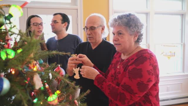 クリスマスイブにクリスマスツリーを飾る大きな2世代の家族は、プライベート住宅の広々とした明るいリビングルームに。若いカップルが話したり、背景に笑ったりするときに装飾を調整す - 義母点の映像素材/bロール