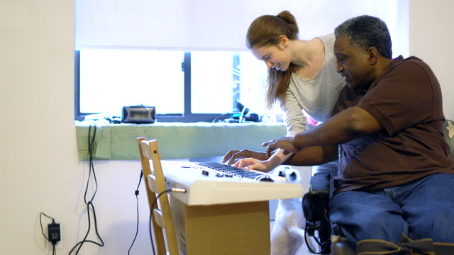 the black disabled man teaching the attractive white teenager girl to play piano keyboard - disability stock videos & royalty-free footage