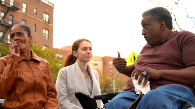 The Black disabled man, veteran in wheelchair, telling the story to the White teenager girl.