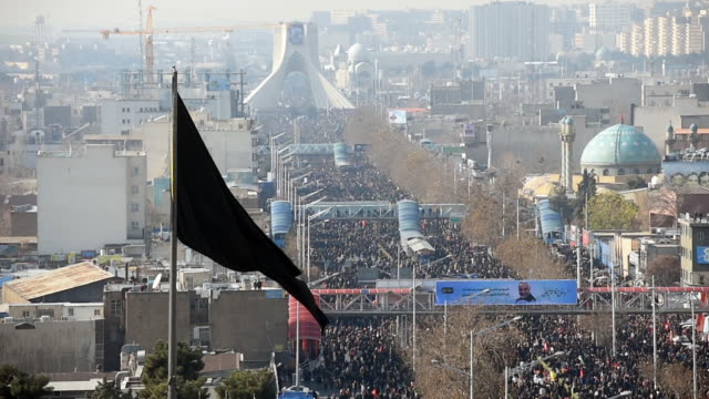 the black standard flies over mourners who have gathered to view the coffins of iranian general qassem soleimani and others killed in the u.s.... - funeral stock videos & royalty-free footage