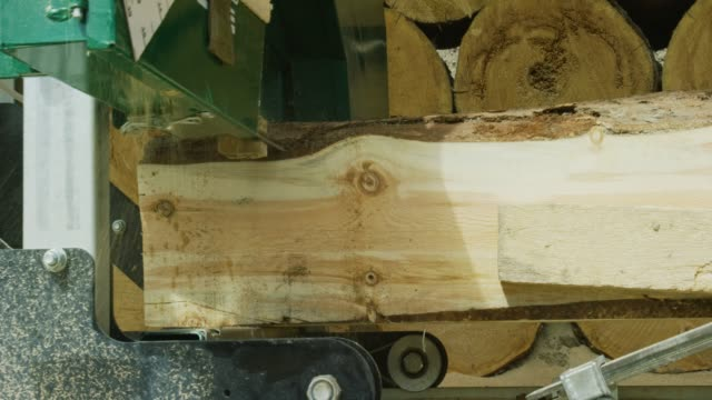 the blade from a log milling machine cuts a log into wooden planks - mill stock videos & royalty-free footage
