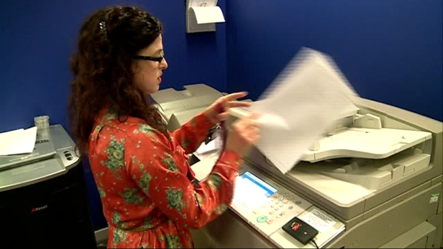 stockvideo's en b-roll-footage met london ext close shots paper out of photocopier various shots amber wells collecting photocopies from machine and making phone call at office desk - kopiëren