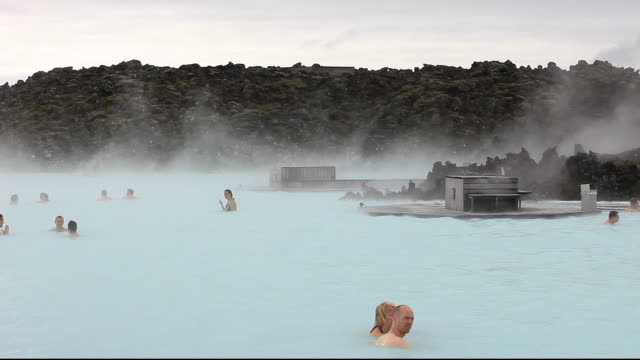 vídeos de stock, filmes e b-roll de the blue lagoon near keflavik in iceland with a geothermal power station in the background. 100% of iceland's electricty is renewable, 70% from hydro, 30% from geothermal. - health farm