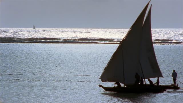 the blue ocean silhouettes men using poles to push their sailboat. - ダウ船点の映像素材/bロール