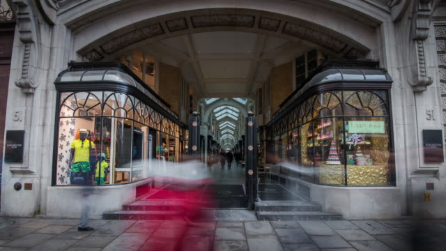 vídeos de stock e filmes b-roll de the blurred shapes of people move rapidly through and past the facade of the famous burlington shopping arcade on piccadilly street - boutique