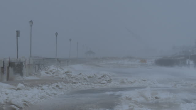 The boardwalk in Belmar NJ is barely visible as strong winds and heavy snow create near whiteout conditions during the historic Blizzard Of 2016