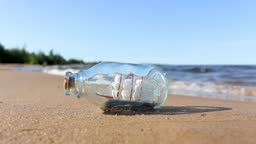 the boat in the bottle is lying on the sand near the water. souvenir from the sea. the concept of pleasant memories and dreams of the sea.
