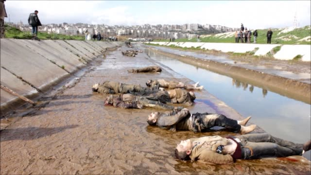 vídeos de stock e filmes b-roll de the bodies of at least 68 men and boys all executed with a single gunshot to the head or neck were found on tuesday in a river in the syrian city of... - execução