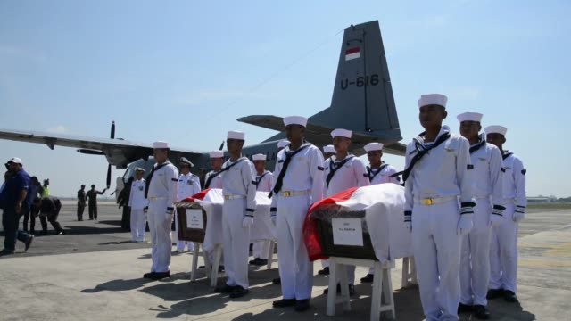 the bodies of eight people killed after an indonesian search and rescue helicopter crashed on sunday arrive at a military airport in surabaya - surabaya stock videos & royalty-free footage