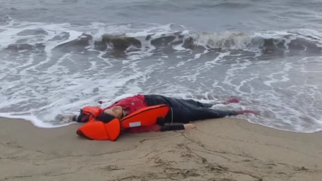 vídeos de stock e filmes b-roll de the body of a refugee is washed ashore on a beach in ayvalik district of balikesir after a boat carrying refugees sank off during their journey to... - crise de migrantes europeia 2015 2016
