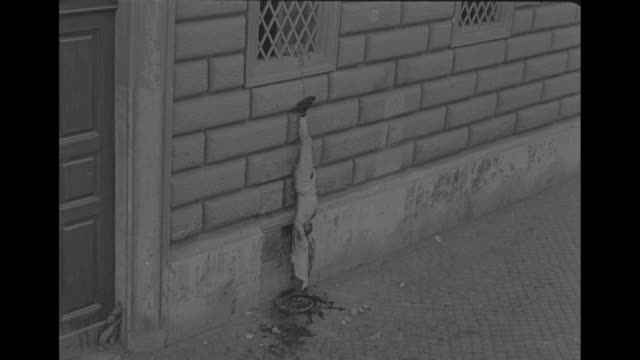vídeos de stock, filmes e b-roll de the body of italian fascist warden donato carretta hangs outside the palace of justice in rome after he was lynched by a mob outside the trial of... - hanging execution