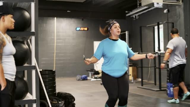 vídeos de stock, filmes e b-roll de a corpo positivo, bonita latino jovem pular corda no ginásio - corda