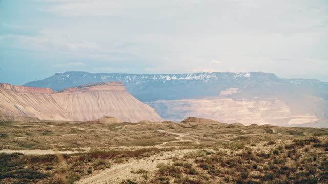 the bookcliffs, mount garfield, and the grand mesa (rocky mountains) and the surrounding high desert of western colorado near grand junction with mountain bike trails in the foreground at sunset - altopiano video stock e b–roll