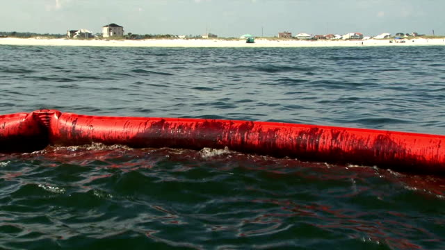 stockvideo's en b-roll-footage met the boom just off shore is shown with oil at its edge / the city's marine police force patrols in boats in search of oil slicks or tarballs on the... - bp
