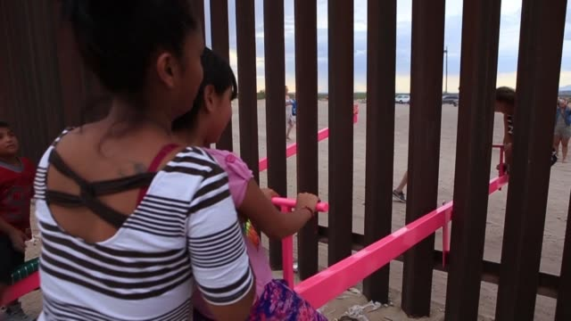 vídeos y material grabado en eventos de stock de the border between us and mexico becomes a playground for north american and mexican families as they take turns on a seesaw called sube y baja in a... - balancín