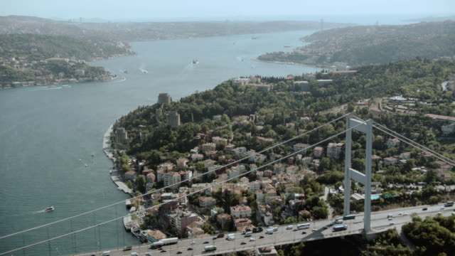 aerial the bosphorus bridge stretching into the city and the bosphorus strait winding out to the sea / istanbul, turkey - july 15 martyrs' bridge stock videos & royalty-free footage