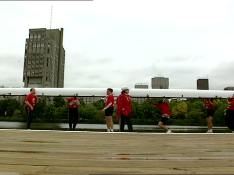 the boston university's racing crew lifts its shell from the river - チャールズ川点の映像素材/bロール
