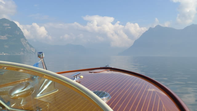 The bow of a classic luxury wooden runabout boat on an Italian lake. - Slow Motion
