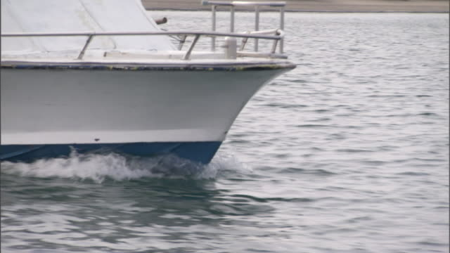 vídeos de stock, filmes e b-roll de the bow of a motorized boat cuts through a calm body of water. - passear sem destino