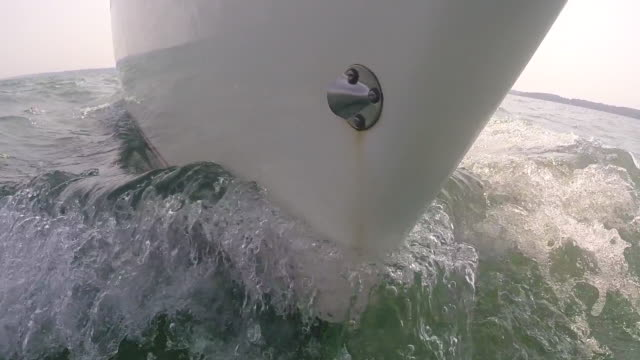 the bow of a sailboat cuts through calm water off the coast of southern england, uk. - fritidsbåt bildbanksvideor och videomaterial från bakom kulisserna