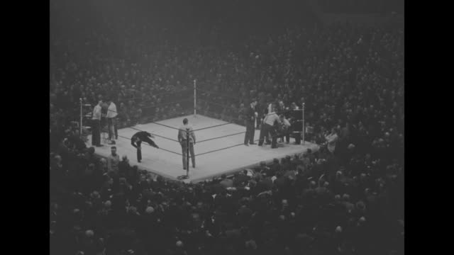 vídeos de stock e filmes b-roll de the boxing ring in the center of thousands of spectators; the men wearing robes enter the ring and go to their respective corners; the fight begins... - madison square garden
