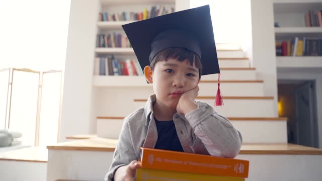 the boy doesn't like to study sitting on the stairs - mortar board stock videos & royalty-free footage