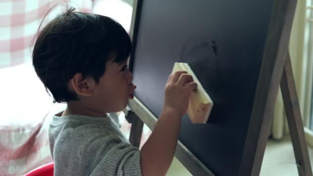 vidéos et rushes de le garçon a effacé la couleur sur le tableau noir. - gomme