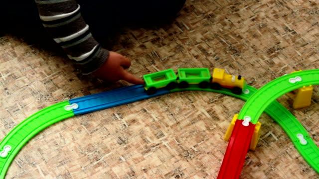 De jongen is een trein rollen op een speelgoed-spoorweg