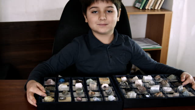 The boy is sitting at the desk with a collection of stones
