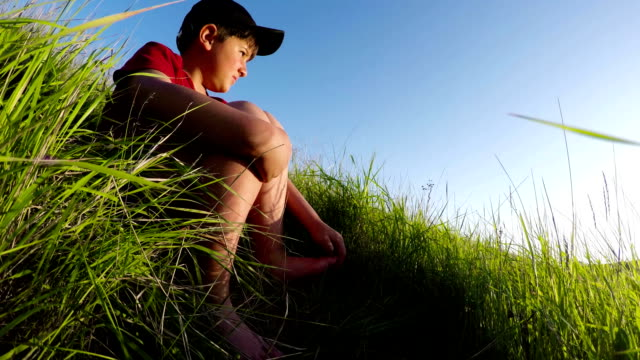 the boy is sitting in the grass barefoot - baby boys stock videos and b-roll footage