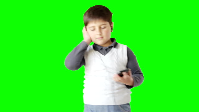 The boy listens to music through headphones and dances