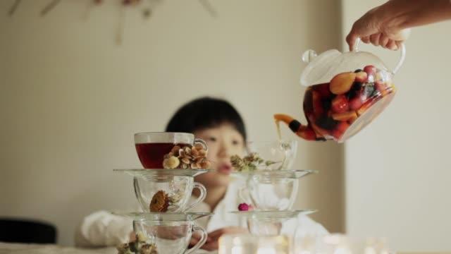 vídeos de stock, filmes e b-roll de the boy looks forward to the moment he pours his fruit tea - vida simples