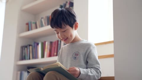 the boy reads a book sitting on the stairs - lesen stock-videos und b-roll-filmmaterial