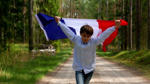 vidéos et rushes de le garçon traverse la forêt avec le drapeau de la france - drapeau