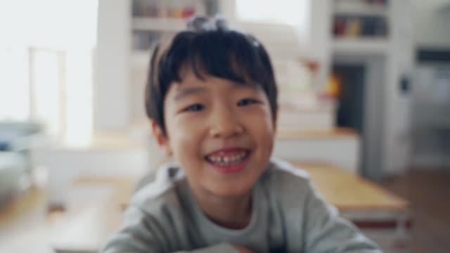 vidéos et rushes de the boy smiles sitting at the desk - east asian ethnicity