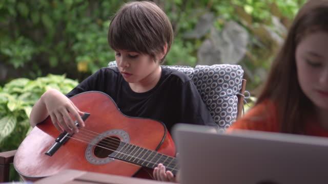 der junge lehrte das mädchen, gitarre zu spielen - torschuss stock-videos und b-roll-filmmaterial
