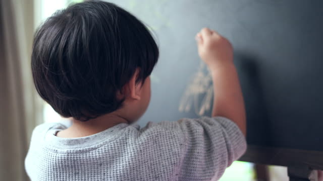 the boy uses chalk to draw on the black board. - gessetto da lavagna video stock e b–roll