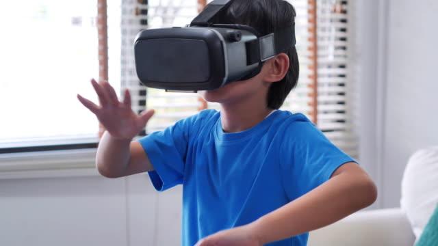 バーチャルリアリティゴーグルを着た少年。バーチャルリアリティを体験する子供たち。vrメガネを見て驚いた小さな男の子。教育、子ども、技術、科学、人々の概念 - 仮想空間点の映像素材/bロール