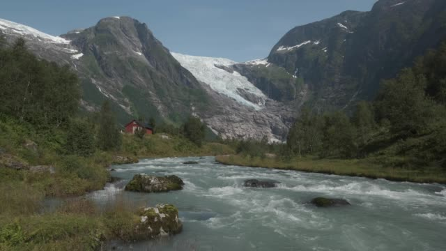 the boyabreen glacier lies above rock it ground smooth and once covered deep in ice while meltwater rushes down a stream past cabins on august 12,... - ice stock videos & royalty-free footage
