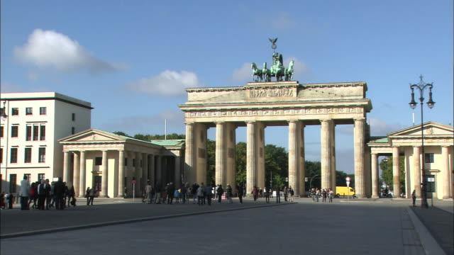 the brandenburg gate towers above pedestrian traffic. - standbildaufnahme stock-videos und b-roll-filmmaterial