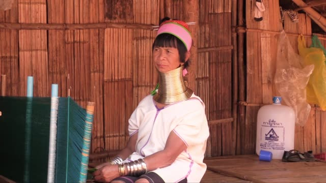 the brass rings round their necks are a continuous spiral and are put on to young female children then the number of rings is increased as the child... - asian tribal culture stock videos and b-roll footage