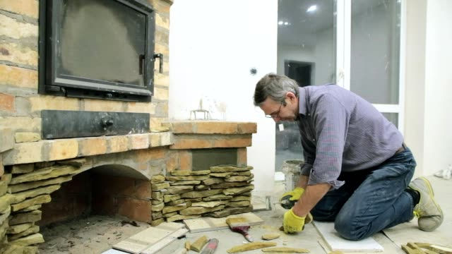 The bricklayer decorates the fireplace with a yellow stone.