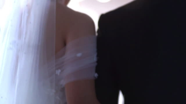the bride and groom walk arm in arm in the wedding ceremony indoors. - arm in arm stock videos & royalty-free footage
