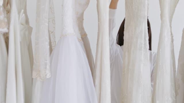 the bride is choosing a wedding dress in the studio. - abito da sposa video stock e b–roll