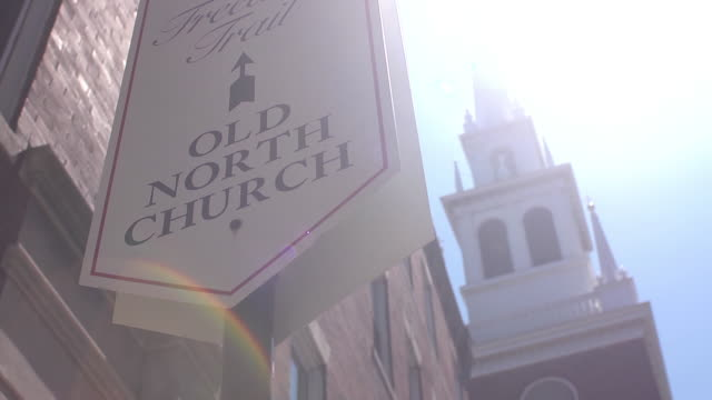 the bright sun hits a sign identifying the old north church behind it. - old north church stock videos & royalty-free footage