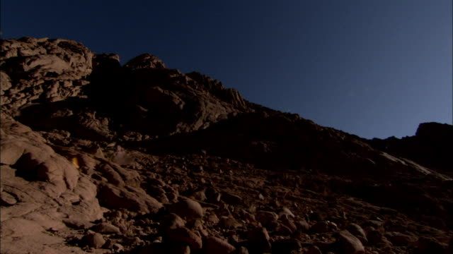 The bright sun shines on a rocky mountain slope. Available in HD.
