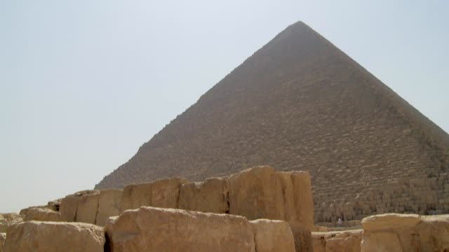the bright sun shines over a pyramid in the giza necropolis. available in hd. - place concerning death stock videos and b-roll footage