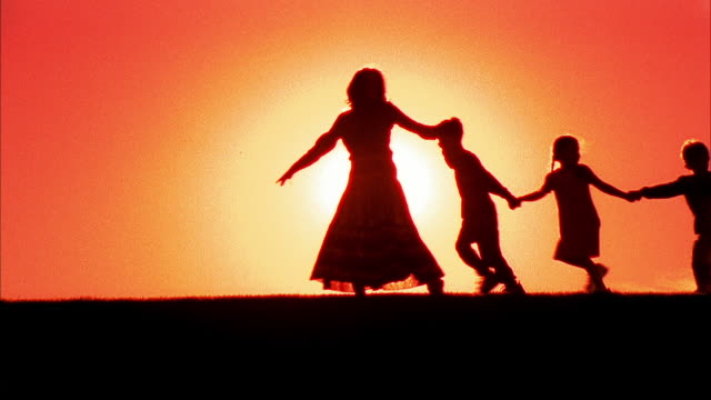 The bright sun silhouettes a mother running while holding hands with her children.