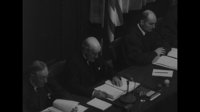 the british justice geoffrey lawrence reads statement during session of the nuremberg trials / a russian reads statement dais with russian british... - processi di norimberga video stock e b–roll
