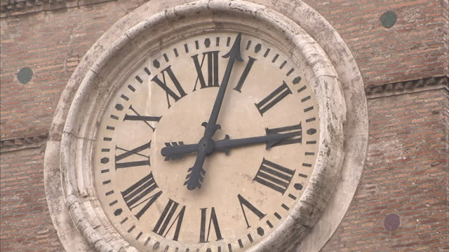 The broken minute hand of an analog clock with Roman numerals moves irregularly.
